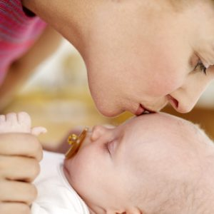Woman Kissing the Top of a Baby's Head (3-6 Months) --- Image by © Royalty-Free/Corbis